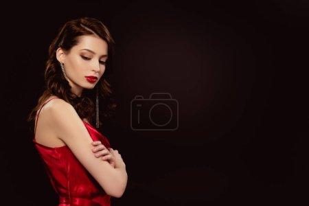 Photo pour Vue latérale de belle femme en robe rouge avec croix bras isolés sur noir - image libre de droit
