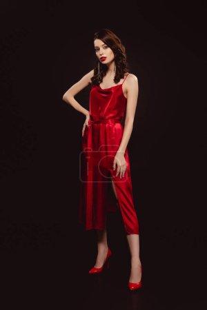 Photo pour Pleine longueur de belle femme en robe rouge regardant la caméra isolée sur noir - image libre de droit