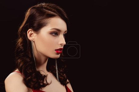 Photo pour Vue latérale d'une élégante fille aux lèvres rouges regardant loin isolée sur noir - image libre de droit