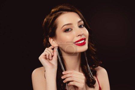 Photo pour Belle femme aux lèvres rouges touchant boucle d'oreille et souriant à la caméra isolée sur noir - image libre de droit