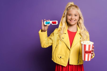 smiling kid holding 3d glasses and bucket with popcorn on purple background