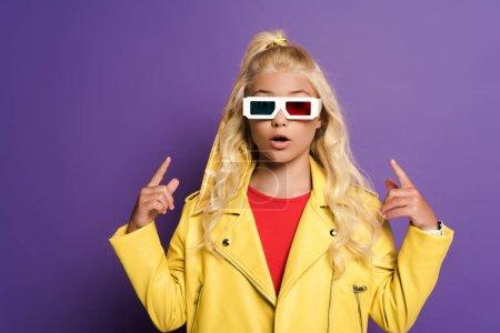 Photo pour Enfant en état de choc avec des lunettes 3D pointant avec les doigts sur fond violet - image libre de droit