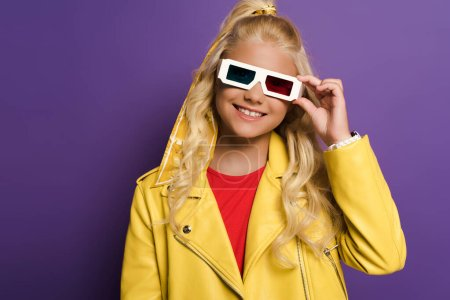 Photo pour Enfant souriant avec des lunettes 3D regardant la caméra sur fond violet - image libre de droit