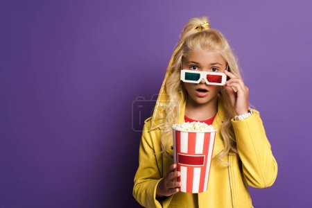 Photo for Shocked kid with 3d glasses holding bucket with popcorn on purple background - Royalty Free Image