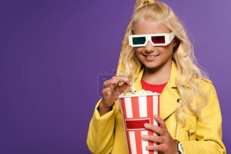 Photo pour Enfant souriant avec des lunettes 3D tenant seau avec pop-corn sur fond violet - image libre de droit