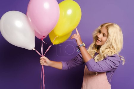 Photo for Smiling kid pointing with fingers at balloon on purple background - Royalty Free Image