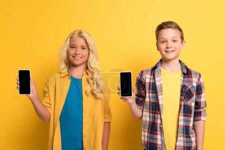 Photo pour Enfants souriants tenant smartphones avec espace de copie sur fond jaune - image libre de droit