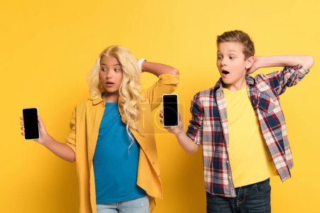 Photo for Surprised kids holding smartphones with copy space on yellow background - Royalty Free Image