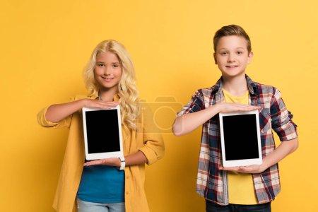 Photo pour Enfants souriants tenant des tablettes numériques avec espace de copie sur fond jaune - image libre de droit