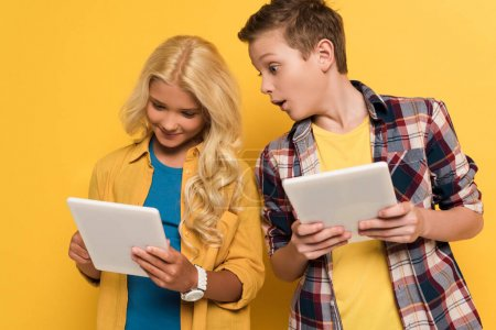 Photo pour Enfant choqué regardant la tablette numérique de son ami souriant sur fond jaune - image libre de droit