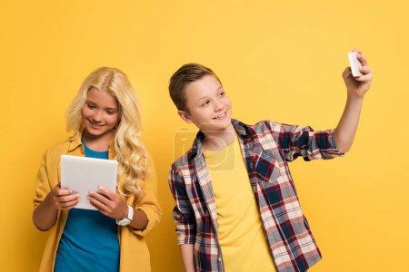 Photo pour Un enfant souriant se prend et son ami se sert d'une tablette numérique sur fond jaune - image libre de droit
