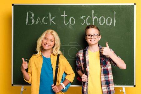 """Photo pour Des écoliers souriants montrant leurs pouces près du tableau avec des lettres de retour à l """"école - image libre de droit"""