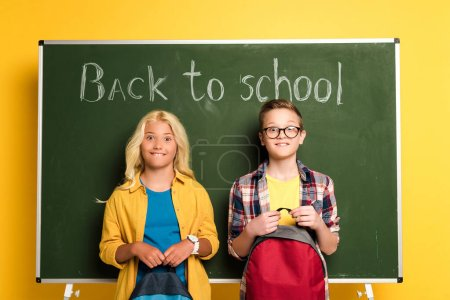 Photo for Smiling schoolkids with backpacks standing near chalkboard with back to school lettering - Royalty Free Image
