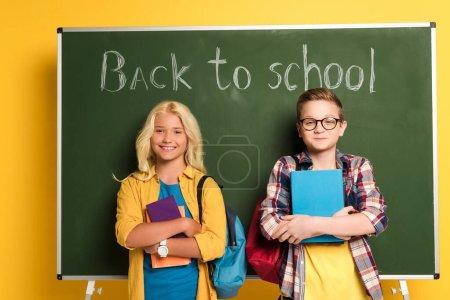 """Photo pour Des écoliers souriants tenant des livres et se tenant près du tableau avec les lettres de retour à l """"école - image libre de droit"""
