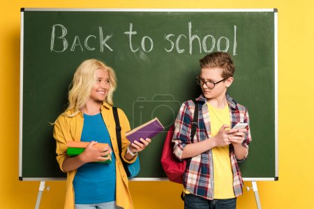 smiling schoolkid giving book to her sad friend with smartphone near chalkboard with back to school lettering