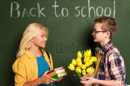 Photo pour Vue latérale d'écoliers souriants tenant des livres et un bouquet près du tableau avec le lettrage de retour à l'école - image libre de droit