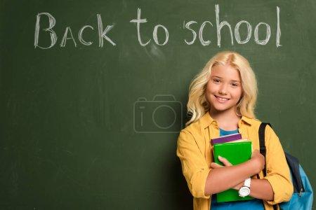 Photo pour Écolière souriante avec des livres debout près du tableau noir avec lettrage de retour à l'école - image libre de droit