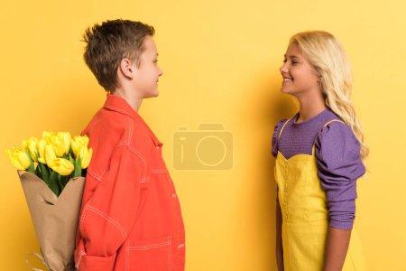 Photo pour Vue latérale d'un garçon souriant cachant un bouquet de son mignon ami sur fond jaune - image libre de droit