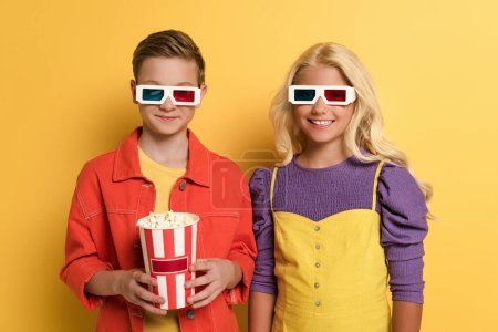 smiling kids with 3d glasses holding popcorn on yellow background