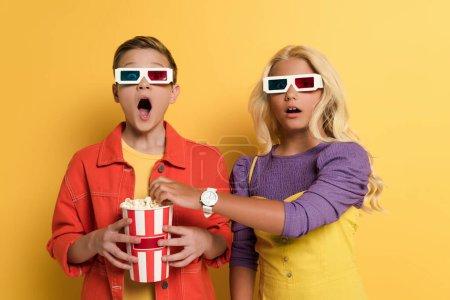 Photo pour Enfants choqués avec des lunettes 3D tenant pop-corn et regardant la caméra sur fond jaune - image libre de droit