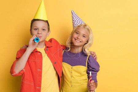 Kind mit Partymütze bläst in Partyhorn und umarmt lächelnden Freund auf gelbem Hintergrund