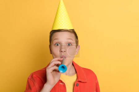 Photo for Kid in party cap blowing in party horn on yellow background - Royalty Free Image