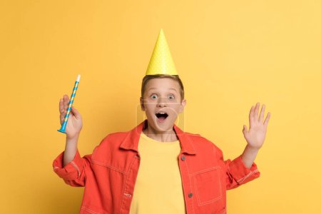 Photo for Shocked kid with party cap holding party horn on yellow background - Royalty Free Image