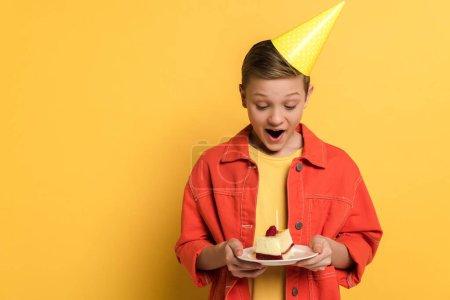Foto de Chocado niño celebración plato con pastel de cumpleaños sobre fondo amarillo - Imagen libre de derechos