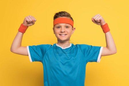 Photo pour Enfant souriant en vêtements de sport montrant un geste fort sur fond jaune - image libre de droit