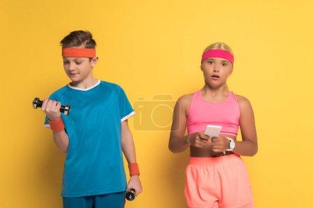 Photo pour Un garçon souriant s'entraîne avec des haltères et son ami choqué tenant un téléphone intelligent sur fond jaune - image libre de droit