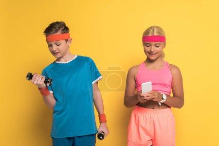 Photo pour Un garçon souriant s'entraîne avec des haltères et son ami tient un téléphone intelligent sur fond jaune - image libre de droit
