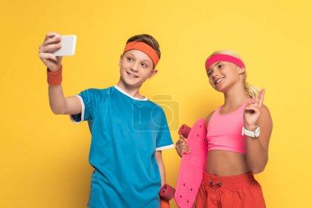 Photo pour Un garçon souriant se prend et son ami tient une planche de penny et montre un geste de paix sur fond jaune - image libre de droit