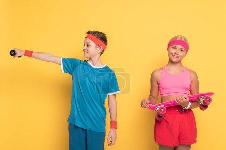 Photo pour Un garçon souriant s'entraîne avec une haltère et son ami tient une planche de penny sur fond jaune - image libre de droit