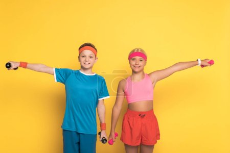 Photo for Smiling kids in sportswear training with dumbbells on yellow background - Royalty Free Image