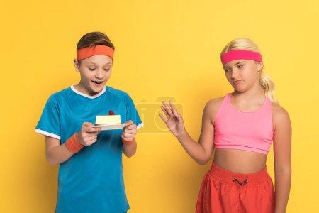 Photo pour Choqué garçon tenant plaque avec gâteau et ami en vêtements de sport ne montrant aucun geste sur fond jaune - image libre de droit