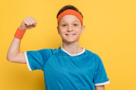 Photo for Smiling kid in sportswear showing strong gesture on yellow background - Royalty Free Image
