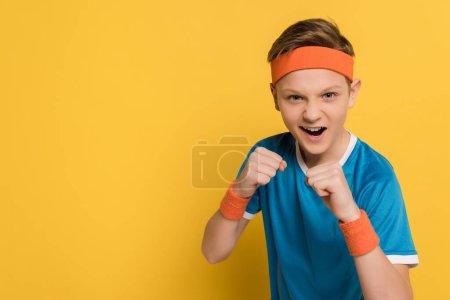 Photo pour Gosse agressif montrant les poings et criant sur fond jaune - image libre de droit