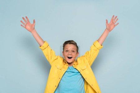 Foto de Niño feliz con manos extendidas mirando a la cámara en fondo azul. - Imagen libre de derechos