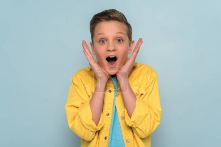 Photo for Shocked and cute kid looking at camera on blue background - Royalty Free Image