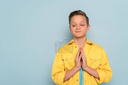 Photo for Smiling and cute kid showing praying hands on blue background - Royalty Free Image