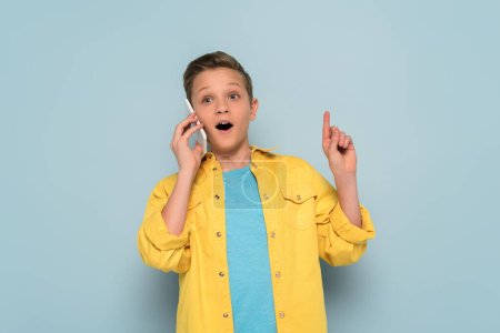 Photo for Surprised kid talking on smartphone and showing idea gesture on blue background - Royalty Free Image
