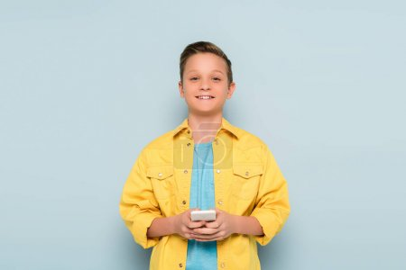 smiling kid holding smartphone and looking at camera on blue background