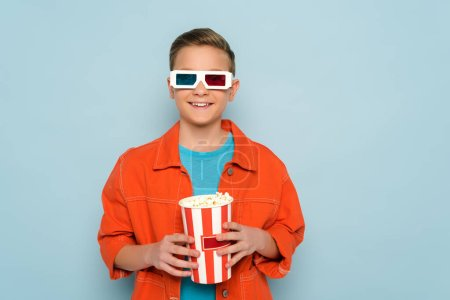 Photo for Smiling kid with 3d glasses holding bucket with popcorn on blue background - Royalty Free Image