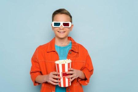 Photo pour Un enfant souriant avec trois verres tenant un seau avec du maïs soufflé sur fond bleu - image libre de droit