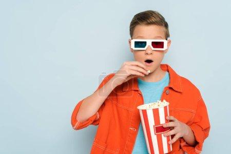 Photo pour Enfant choqué avec des lunettes 3D manger du pop-corn sur fond bleu - image libre de droit