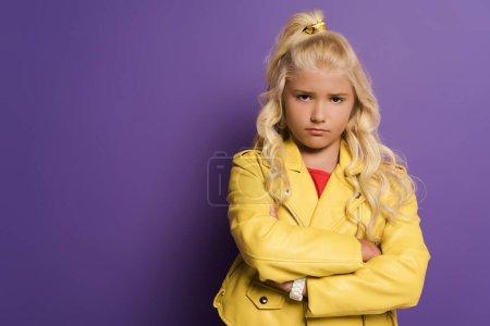 Photo pour Offensé gamin avec les bras croisés regardant caméra sur fond violet - image libre de droit