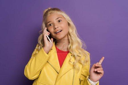 Photo pour Enfant souriant parlant sur smartphone et montrant signe d'idée sur fond violet - image libre de droit