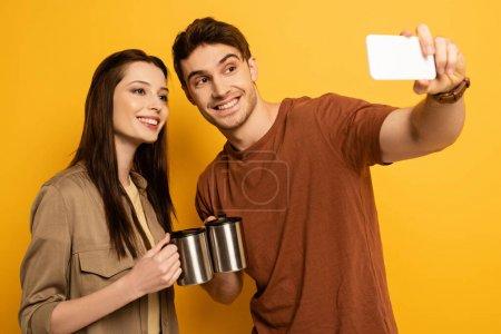 Photo pour Couple de voyageurs souriants avec tasses avec prise de café selfie sur smartphone sur jaune - image libre de droit