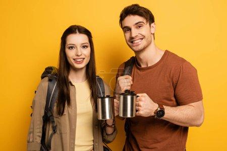 pareja de turistas sonrientes con mochilas sosteniendo tazas con café en amarillo