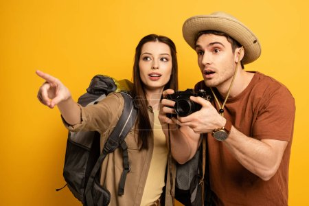Photo for Couple of shocked tourists with photo camera pointing on yellow - Royalty Free Image